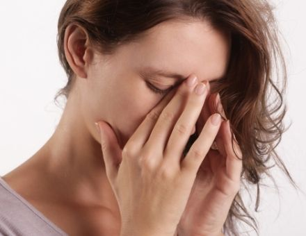 Woman holding her upper nose, perhaps with a perforated sinus and infection - for information from Burba Dental in the Boston, MA area