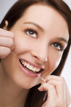 Young Woman flossing teeth close up shoot