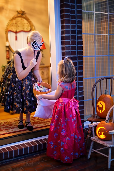 Little girl trick-or-treating at a door. Woman answering the door has candy and a mask.